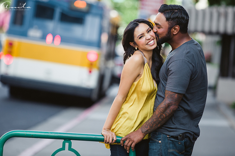 Couple smiles in Downtown Sacramento with city bus in background